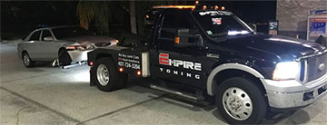 Orlando Towing Service truck towing a wrecked passenger vehcile - Empire Towing, LLC