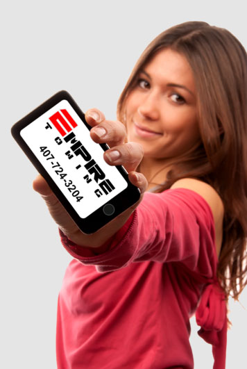 Woman holding a phone showing the Empire Towing logo and phone number